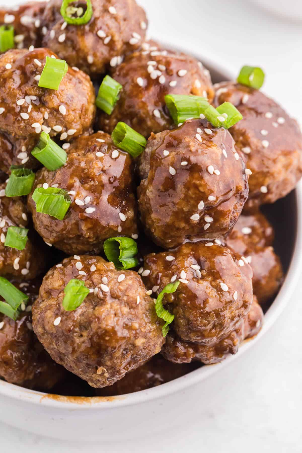 Ginger Meatballs - Add this Asian meatball recipe to your next party menu! Homemade beef meatballs with zesty ginger are smothered in sweet and tangy stir fry sauce. Yum!
