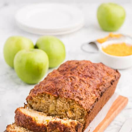 A loaf of apple cheddar bread with slices cut on the end