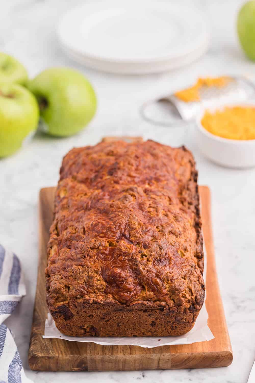 A loaf of apple cheddar bread on a cutting board