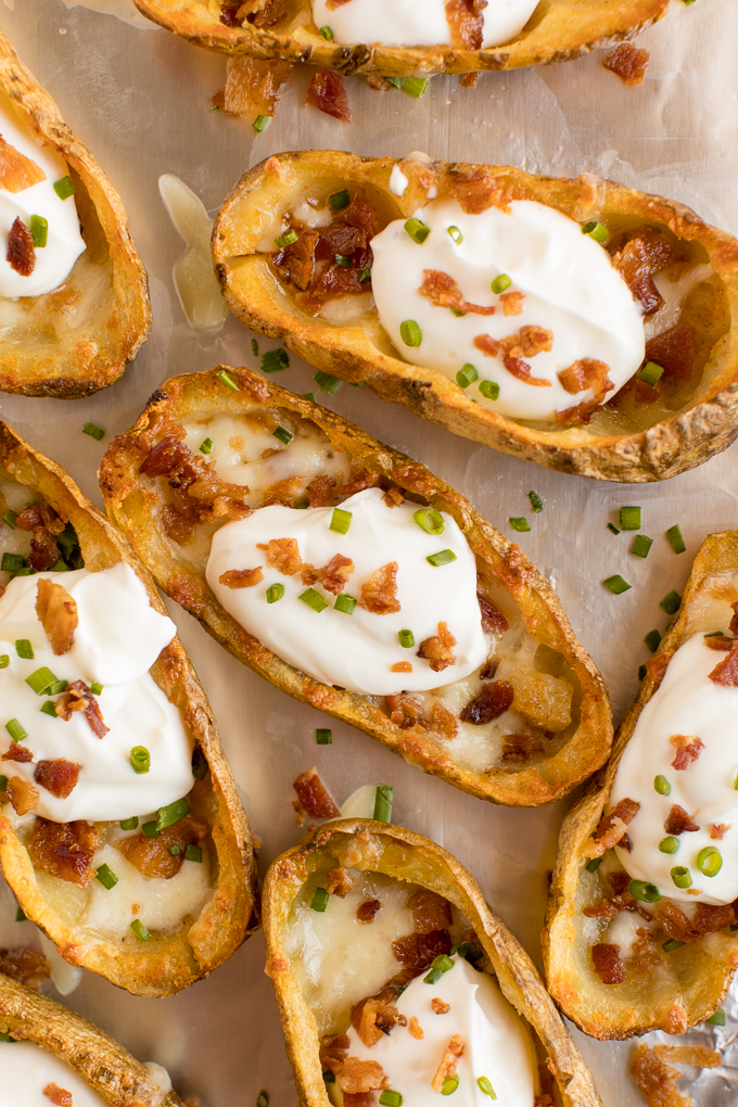 Cheesy Potato Skins - Topped with sour cream, tasty bacon and fresh green onions, this appetizer recipe is a crowd-pleasing classic.