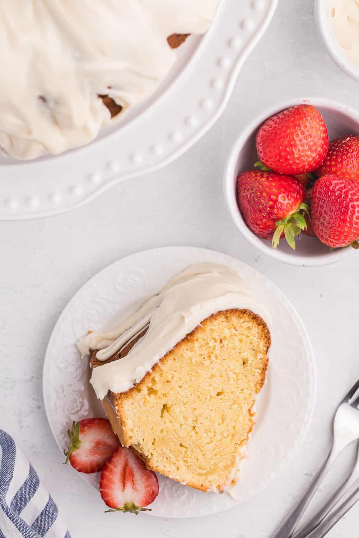 A slice of vanilla cream cheese cake with strawberries