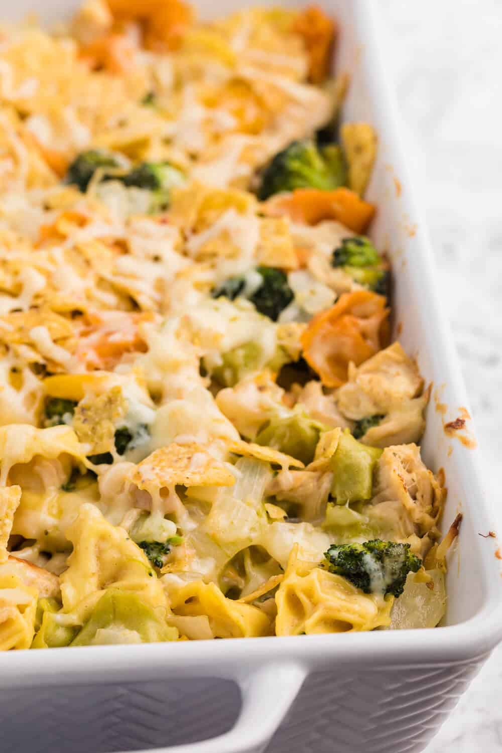 Santa Fe Chicken Tortellini Casserole - Tortellini pasta with veggies and chicken enveloped in a creamy sauce and topped with crunchy tortilla chips. An easy family dinner recipe ready in under 1 hour.