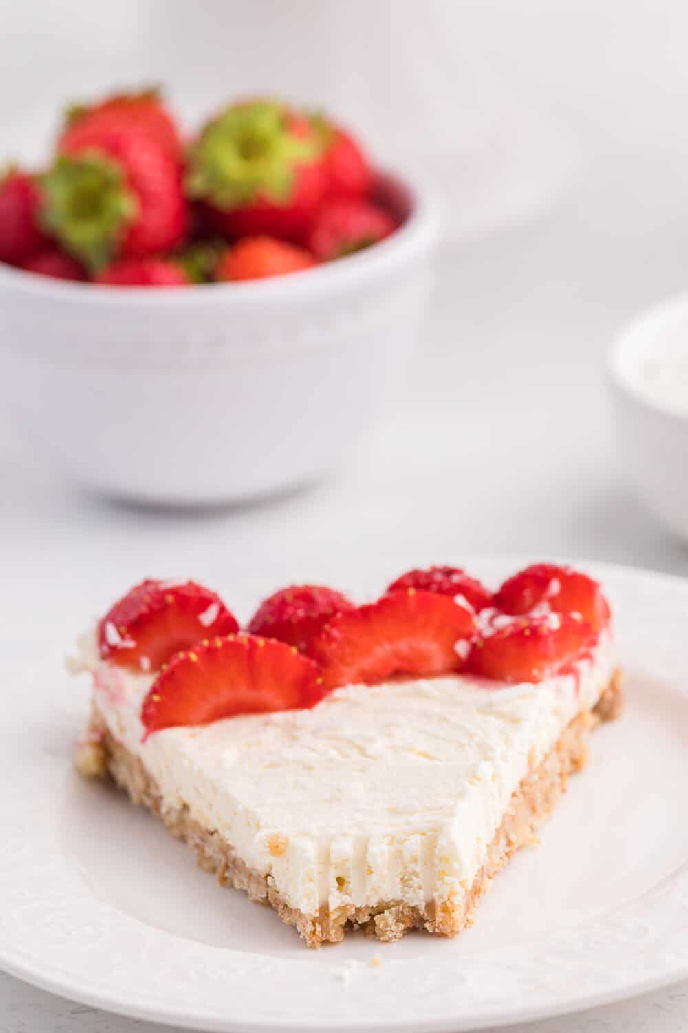 A slice of no-bake strawberry cheesecake with a bite out of the end