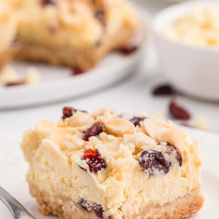 A white chocolate cranberry cheesecake bar on a white plate