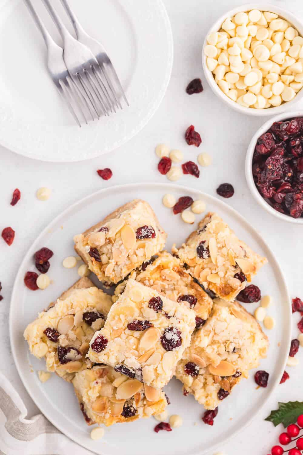 A plate of cut white chocolate cranberry cheesecake bars