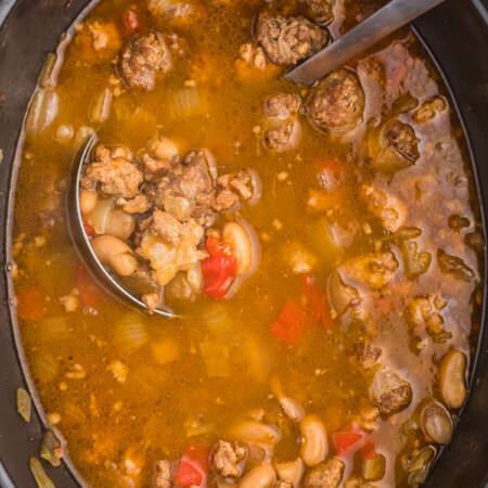 Chicken Sausage Soup is the perfect soup to whip up on a chilly day. This slow cooker soup recipe is full of beans, garlic, onion and beer for one savory soup. Pair with dinner rolls and dive in.