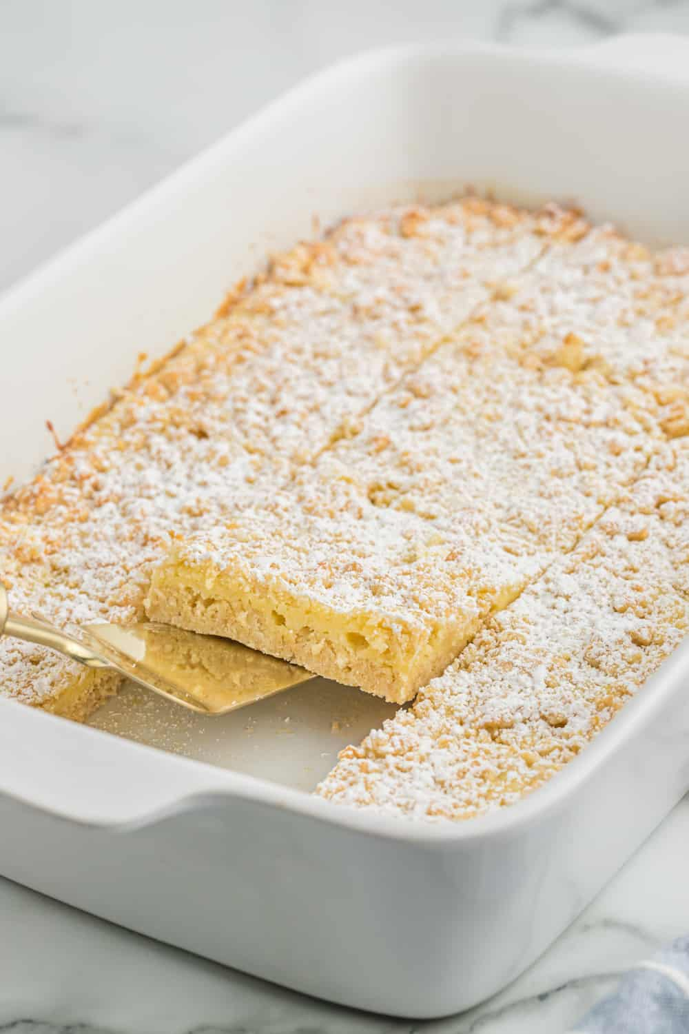 french vanilla cream bars in a casserole pan with a spatula serving a piece