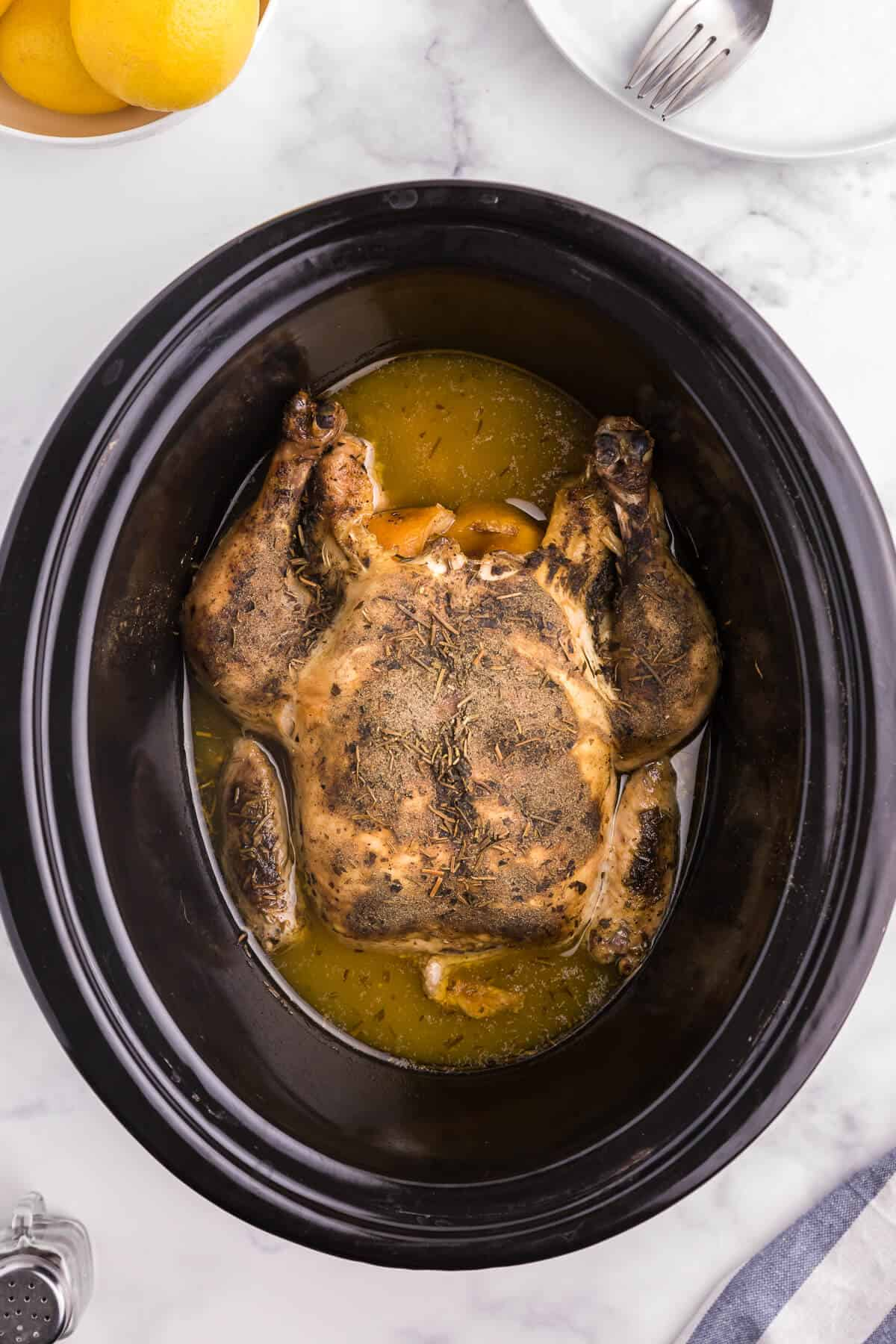 Lemon Herb Slow Cooker Chicken - Roast a whole chicken in your Crockpot! This easy chicken recipe is so much juicier with lemon juice and a succulent herb blend.