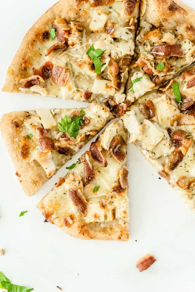 Chicken Caesar Pizza - Your favorite salad can also be your favorite homemade pizza recipe! Ditch the lettuce and make this simple crowdpleaser. Imagine pizza crust smothered in creamy Caesar dressing, topped with bacon, chicken and cheese!
