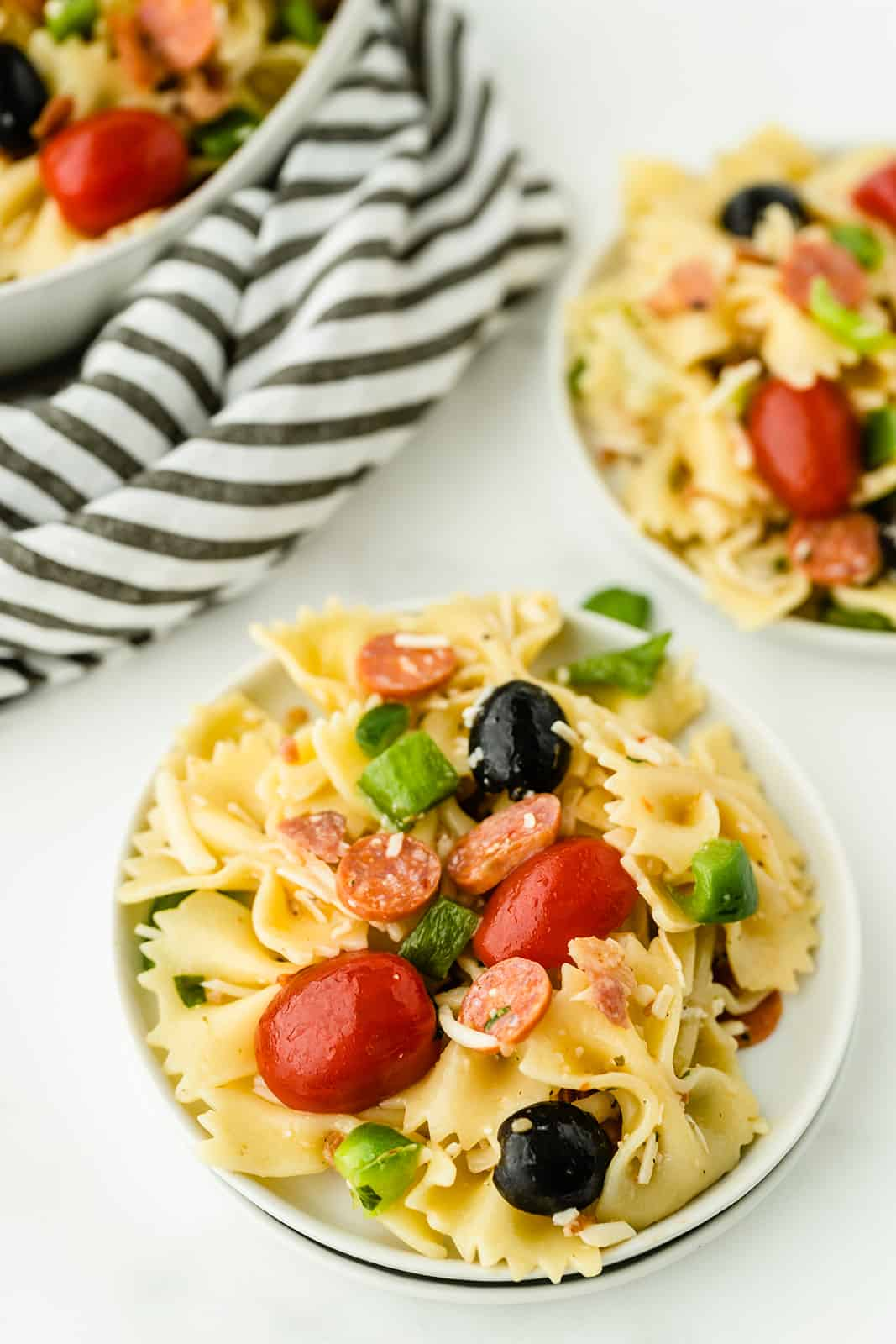 Pizza Pasta Salad - A perfect summer dish with all the best pizza flavors! Salty pepperoni and olives are coated in tangy Italian dressing and covered in cheese.
