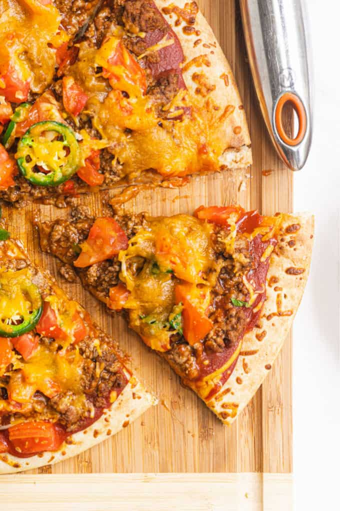 Taco Pizza - Bring Mexican night to your pizzas! Loaded with ground beef, cheese, and tons of veggies, you won't even miss the tortillas.