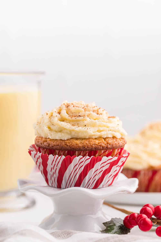 Side shot of eggnog cupcake on a white cupcake stand