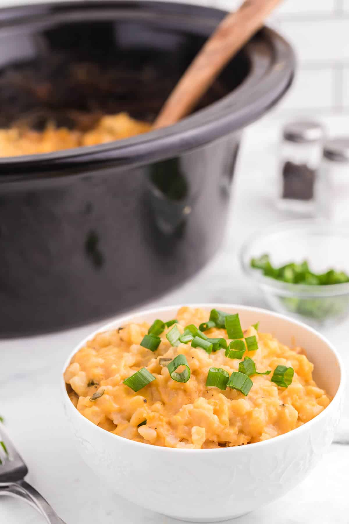 Slow Cooker Cheesy Potatoes is a delicious and hearty side dish to pair with your weeknight dinner. Frozen hash browns, canned cheese soup and a few other ingredients are all you need for this easy potato recipe.