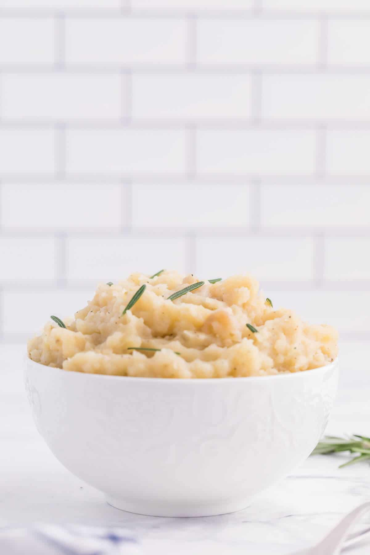 Slow Cooker Rosemary Garlic Mashed Potatoes - Make the creamiest mashed potatoes in your Crockpot! You'll love the rich, garlicky flavor in every bite for a delicious fall side dish.