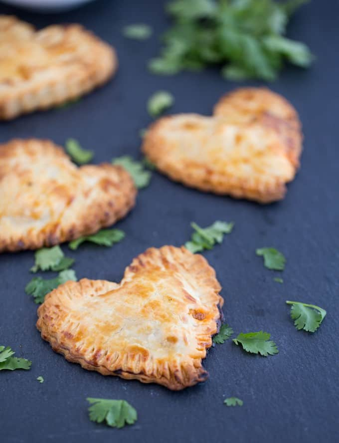 Butter Chicken Hand Pies - The best homemade Valentine's Day dinner ever! Make these heart pies with love and be done in 40 minutes flat. Creamy, flavourful Butter Chicken is stuffed inside a golden, flaky heart shaped crust!