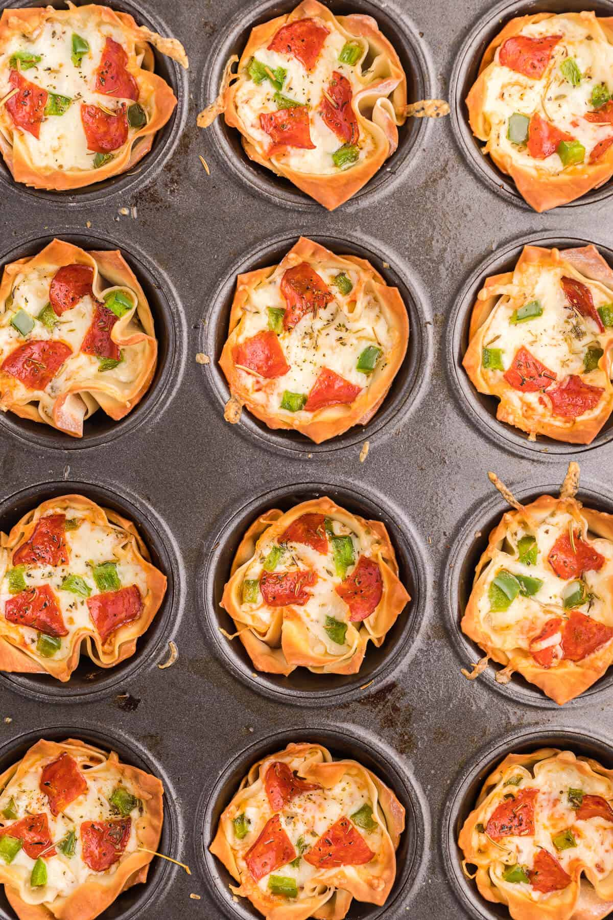 Pizza Wonton Cups Recipe - East meets West in this simple crunchy appetizer. A crispy wonton is filled with cheesy pizza goodness with any toppings you want!