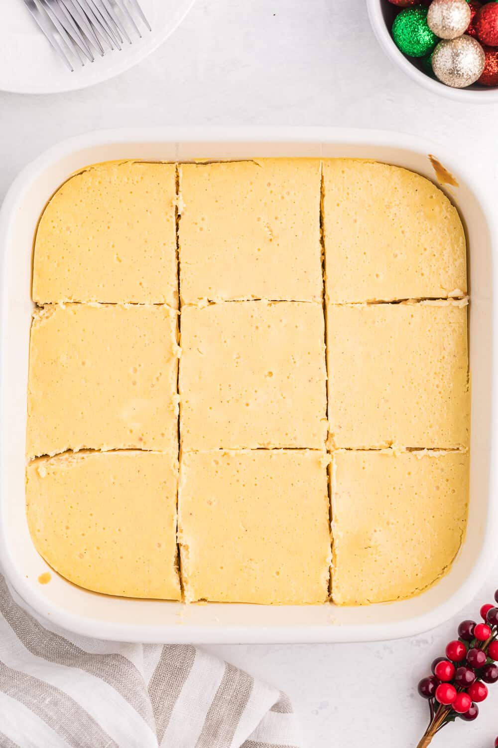 Eggnog cheesecake bars in a casserole pan with cut slices into the squares.