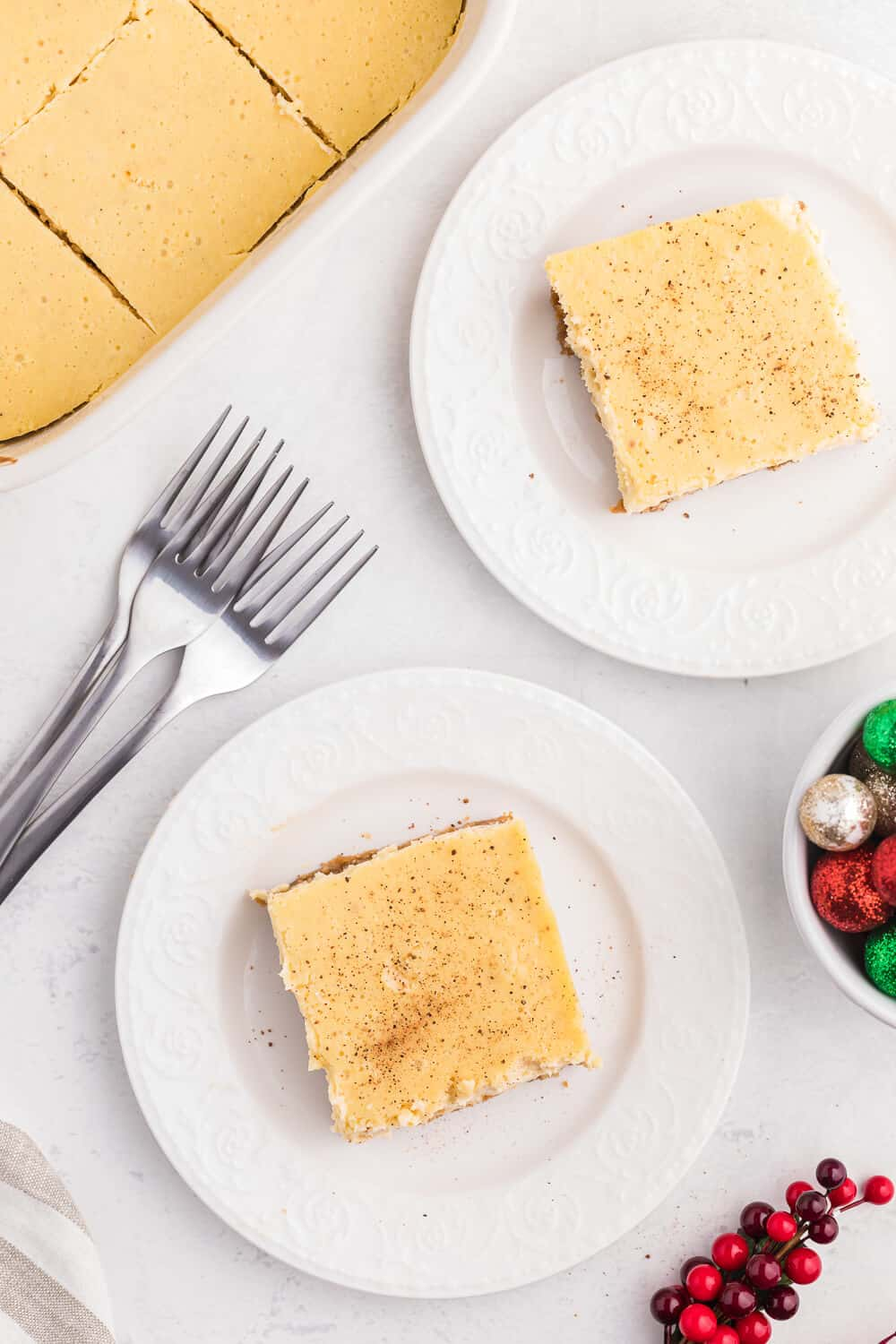 overhead of two slices of eggnog cheesecake bars on white plates.