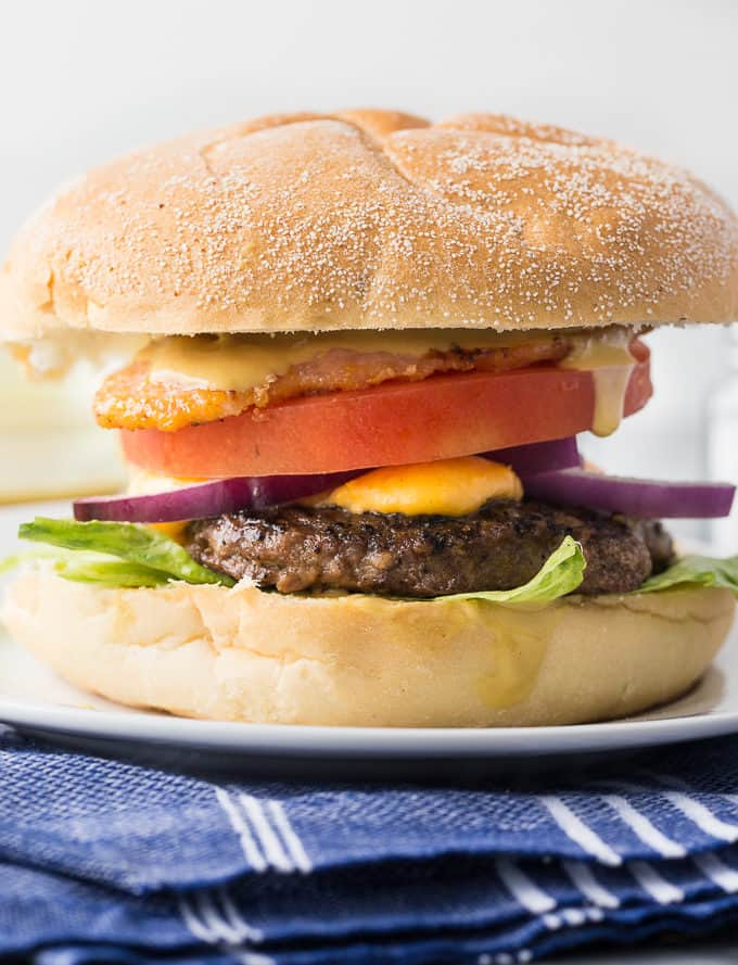 Ultimate Ontario Burger - A juicy burger topped with melted cheddar cheese curds, Maple Mustard, Peameal bacon and fresh local veggies.