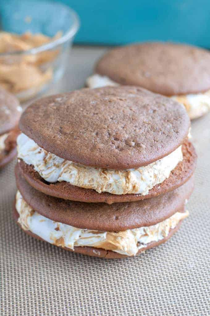 Chocolate Peanut Butter Whoopie Pies - A dessert lover's dream! Marshmallow fluff swirled with peanut butter sandwiched between two soft chocolate cookies.