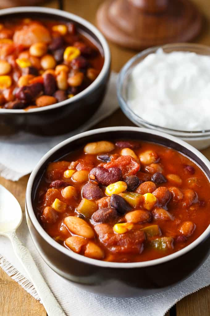 Bean Chili - The heartiest meat-free chili recipe! Use four different kinds of canned beans in this comfort food classic with peppers, corn, and tomatoes.