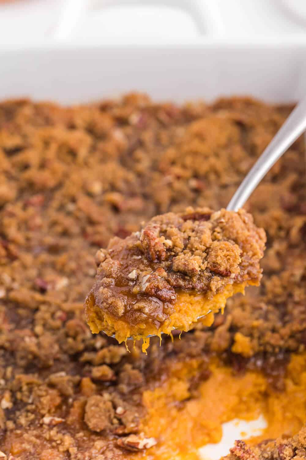 a serving spoon with sweet potato casserole on it