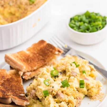 Scrambled Egg Casserole - Soft oven-scrambled eggs with ham, green onion, cheddar and mushrooms are baked under a crispy, toasted layer of bread crumbs. A delicious and decadent change from bread-based breakfast casseroles.