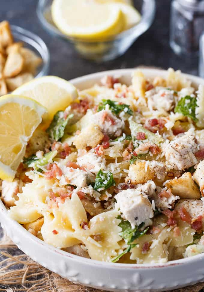 Chicken Caesar Pasta Salad - The BBQ side you'll make every summer! Take your favorite salad poolside with this spin on bowtie pasta salad with homemade caesar dressing and crispy bacon.