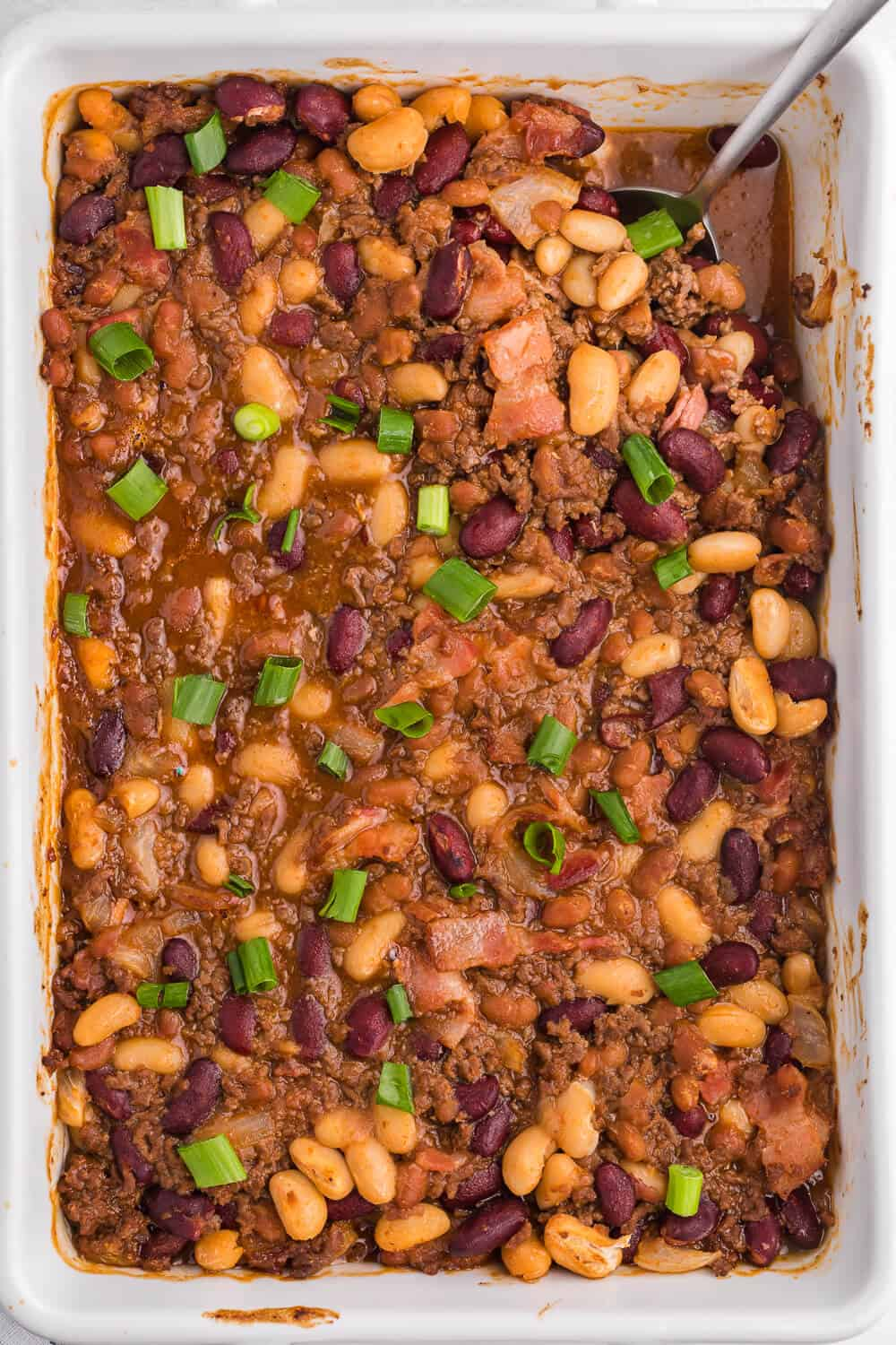bean casserole in a casserole pan with a serving spoon