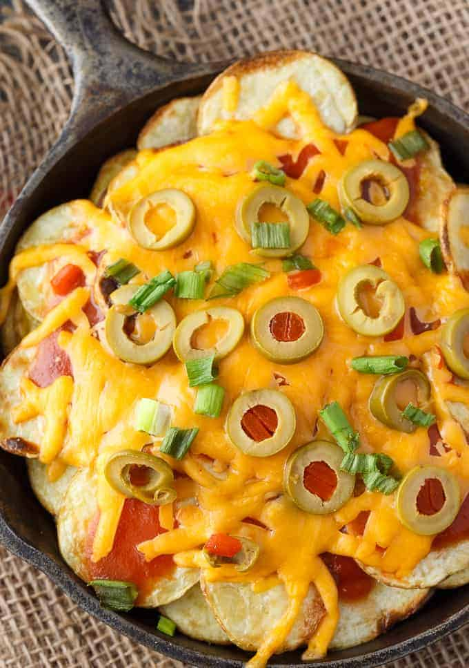 Potato Nachos - Crispy, flavorful potatoes loaded with taco sauce, green olives, green onions and lots of melty cheddar cheese. The perfect appetizer!