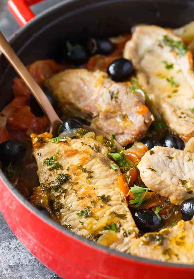 Savory Pork Chops - Tender pork chops are cooked in a savory sauce filled with tomatoes, garlic, green peppers, black olives and spices. A super easy weeknight meal for your family.