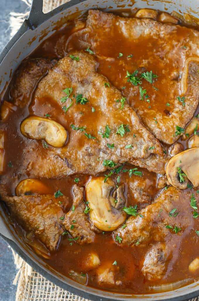 Mushroom Swiss Steak - Tender steak, mushrooms and onions are enveloped in a sweet and savory gravy. This easy dinner recipe pairs nicely with mashed potatoes to sop up all the delicious gravy.
