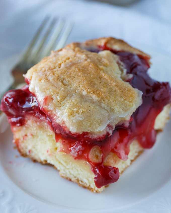 Cherry Cake - An easy, old-fashioned recipe that everyone adores! Moist cake is topped with sweet cherry pie filling and a sweet vanilla glaze.