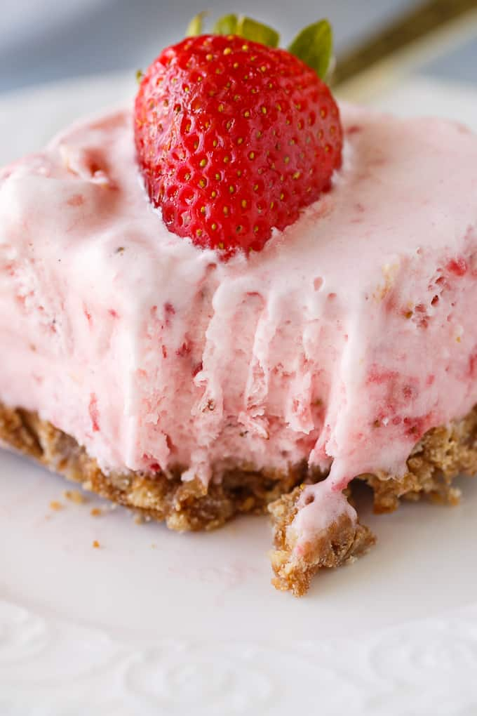 Frozen Strawberry Fluff - A sweet summer frozen delight! A buttery cookie crust is topped by a creamy, cold strawberry layer of yum.