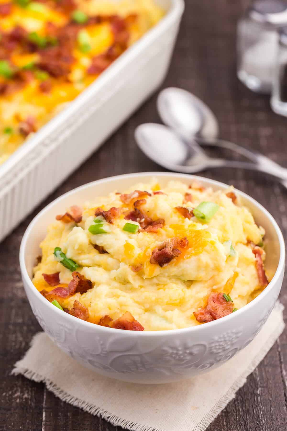 Loaded Mashed Potatoes - The ultimate comfort food side dish recipe. This homemade casserole is extra indulgent with loads of cheese, bacon and sour cream.