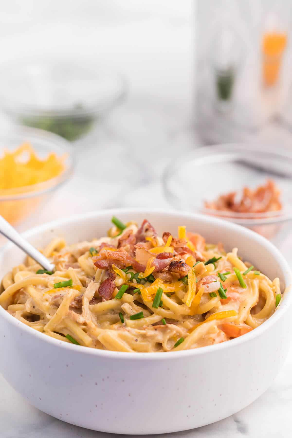 Crack Chicken Spaghetti Recipe - One bite and you'll be hooked! This easy and delicious dinner recipe is creamy, cheesy and addictive. It's loaded with chicken, bacon, veggies and spaghetti noodles in a flavorful cream cheese based sauce.