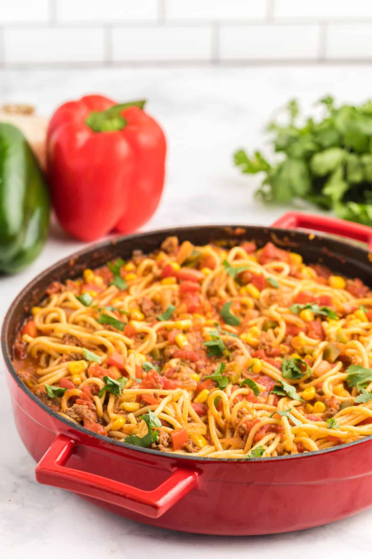Mexican Spaghetti Recipe - This easy taco pasta recipe is filled with cheesy ground beef, taco seasoning, peppers, corn, tomatoes and noodles. It's simple to make with just the right amount of spice. The perfect family dinner recipe.
