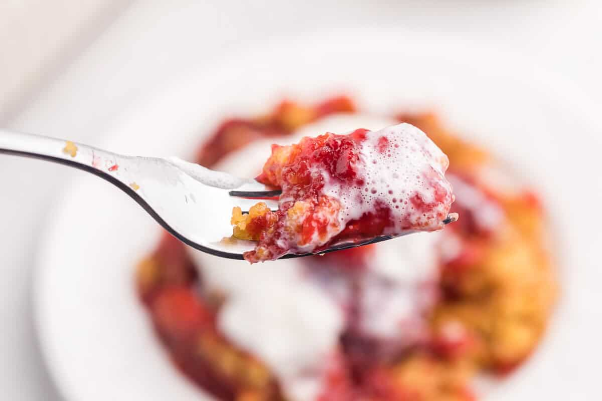 Strawberry Dump Cake Recipe - Only 4 ingredients in this simple sweet dessert! Cake mix and strawberry pie filling come together to make a luscious strawberry cake with little effort. One of the easiest dump cake recipes ever!