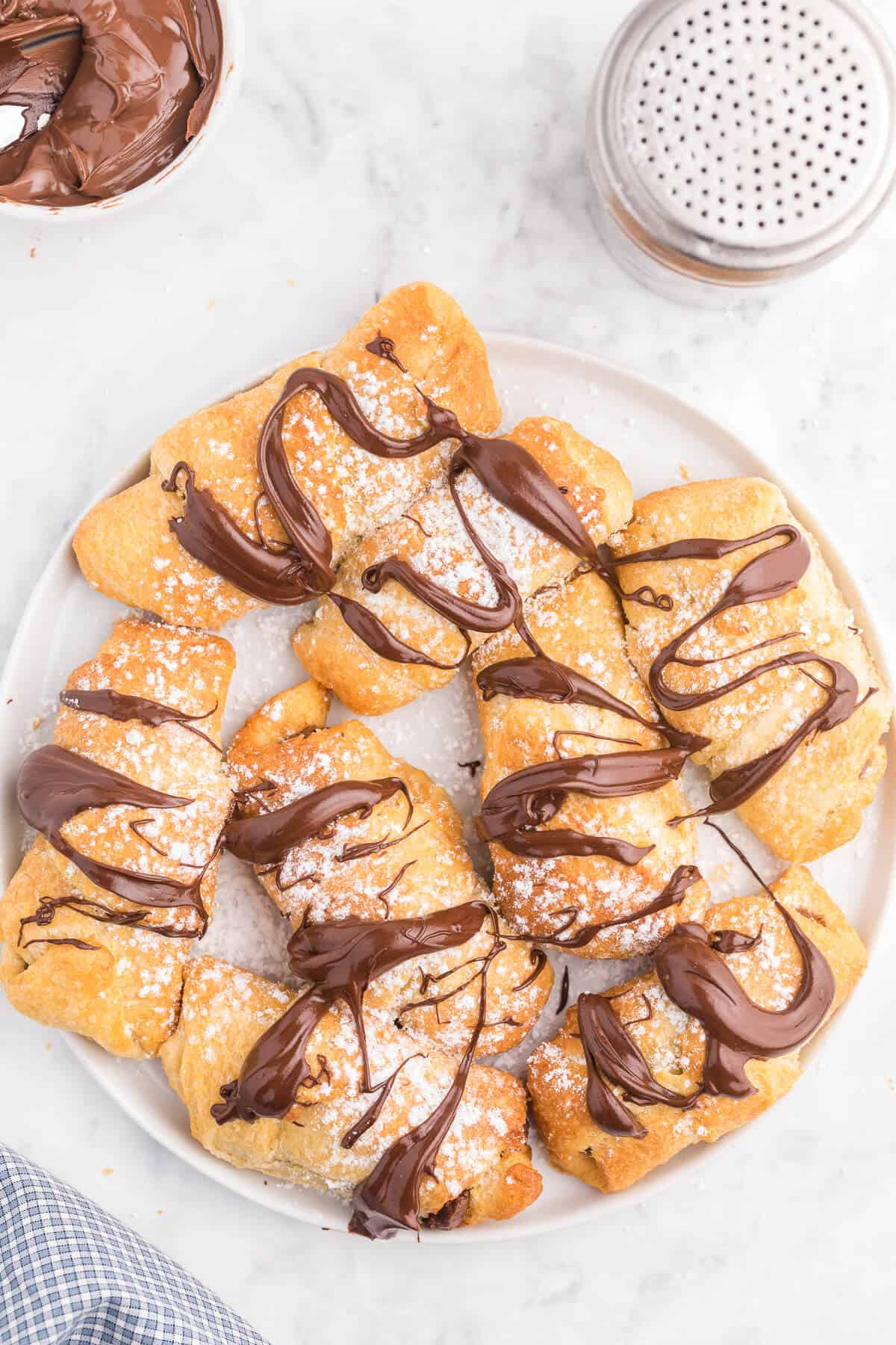 Air Fryer Chocolate Crescent Rolls Recipe - Make these chocolate stuffed crescent rolls in your air fryer. Wrap Pillsbury crescent roll dough around a spoonful of sweet and rich Nutella. Ready to eat in minutes! Such a delicious and easy dessert everyone loves.