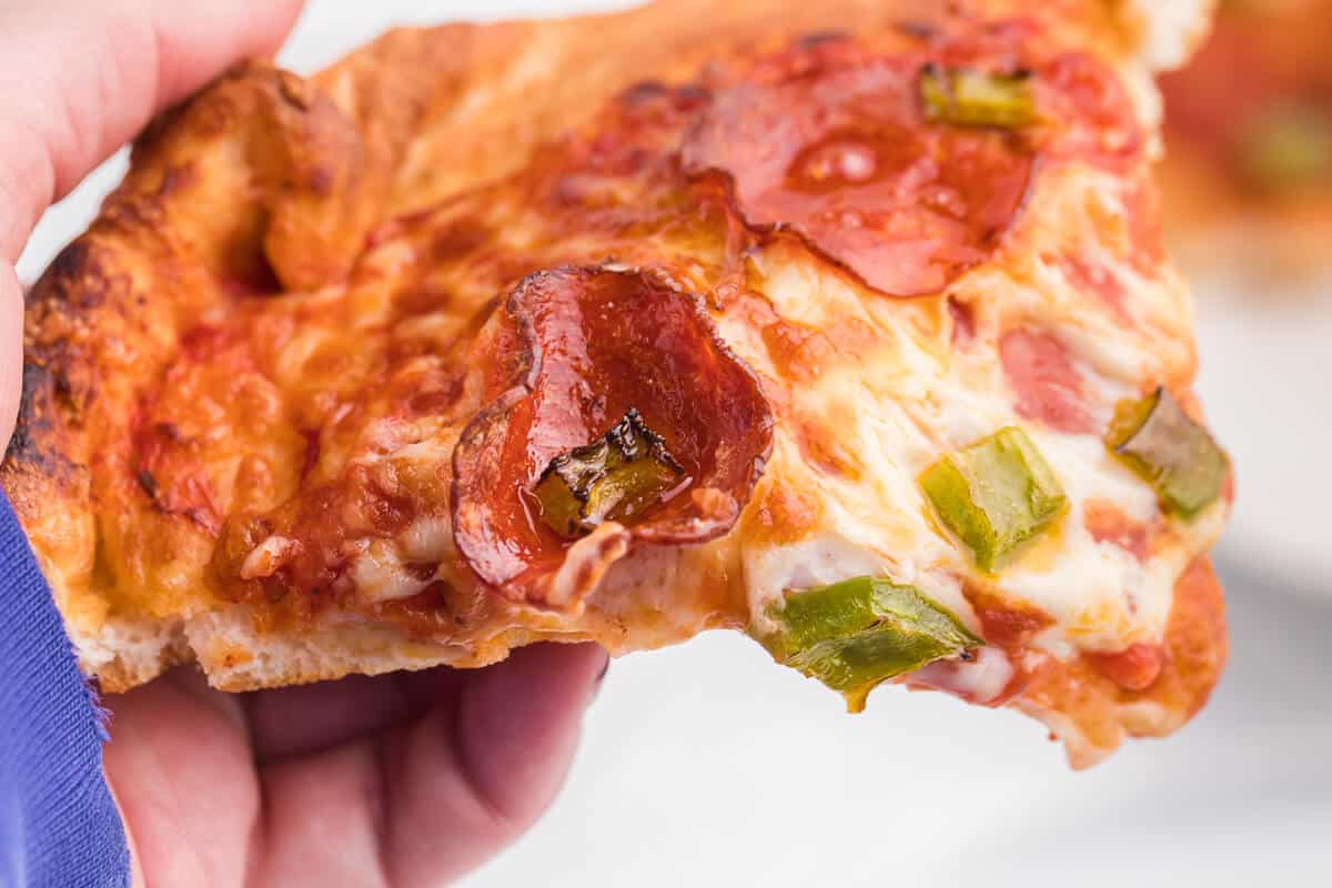 Air Fryer Pizza Recipe - Use premade pizza dough to make this better than delivery pizza right in your air fryer! This recipe makes two individual pizzas that are ready to eat in minutes.