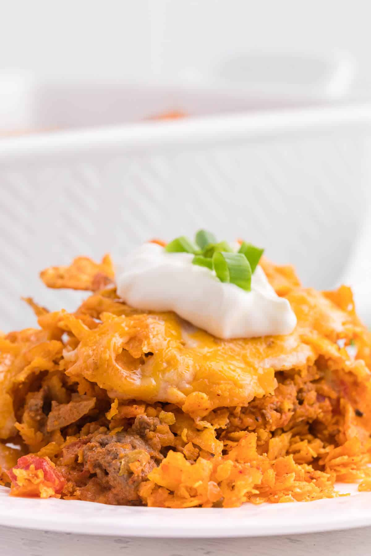 Doritos Casserole Recipe - Take Mexican night to a whole new level with this easy taco bake recipe. Made with ground beef, sour cream, spices and loads of cheese, it's zesty with hearty Tex Mex flavor. A yummy dinner recipe your family will love!