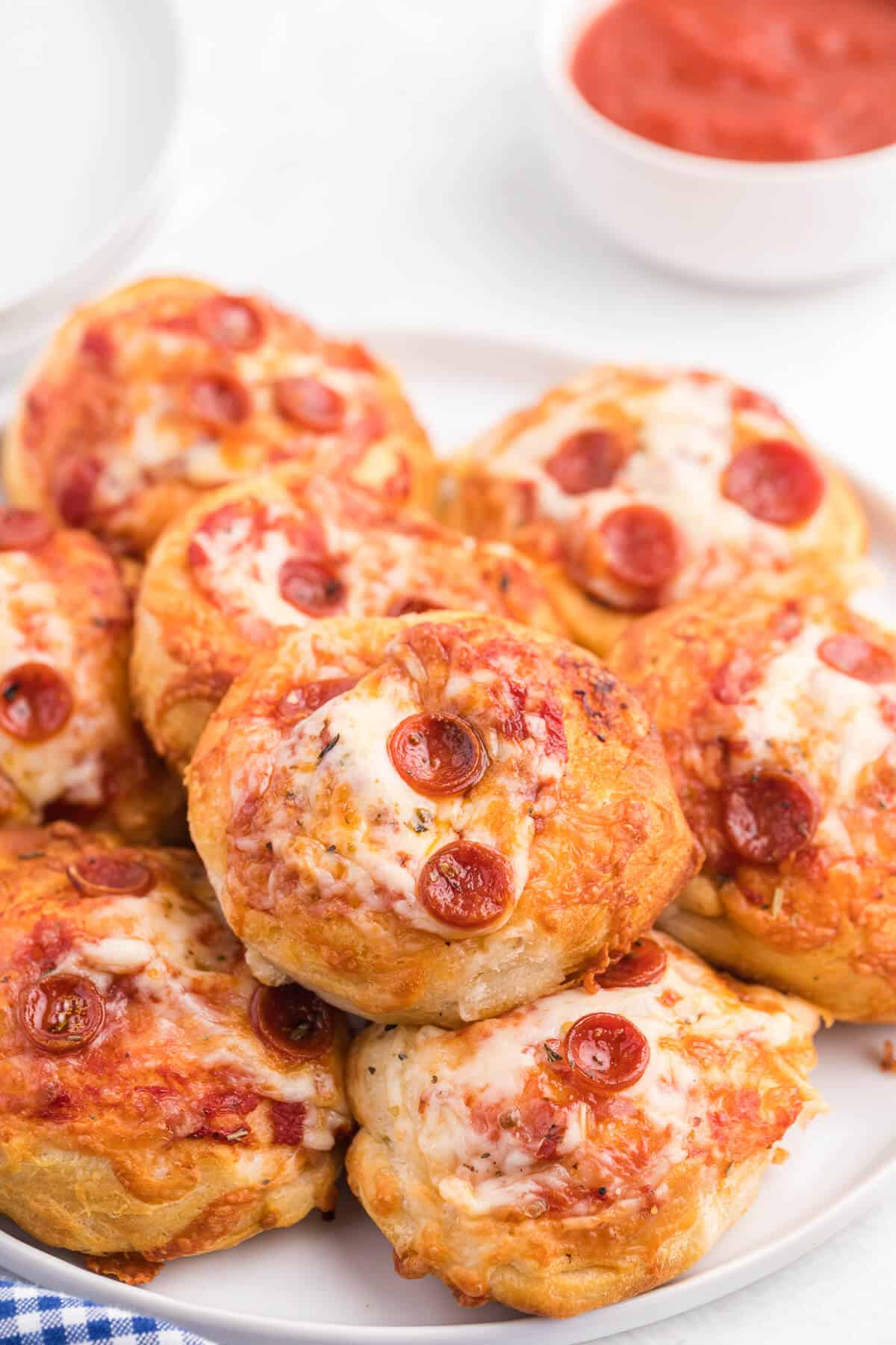 Air Fryer Pizza Buns - This simple recipe is perfect for snacking, an appetizer or for your kids' school lunch. Air fried to golden perfection, these savory buns are easy to make with refrigerated dough, pizza sauce, mozzarella cheese and pepperoni.