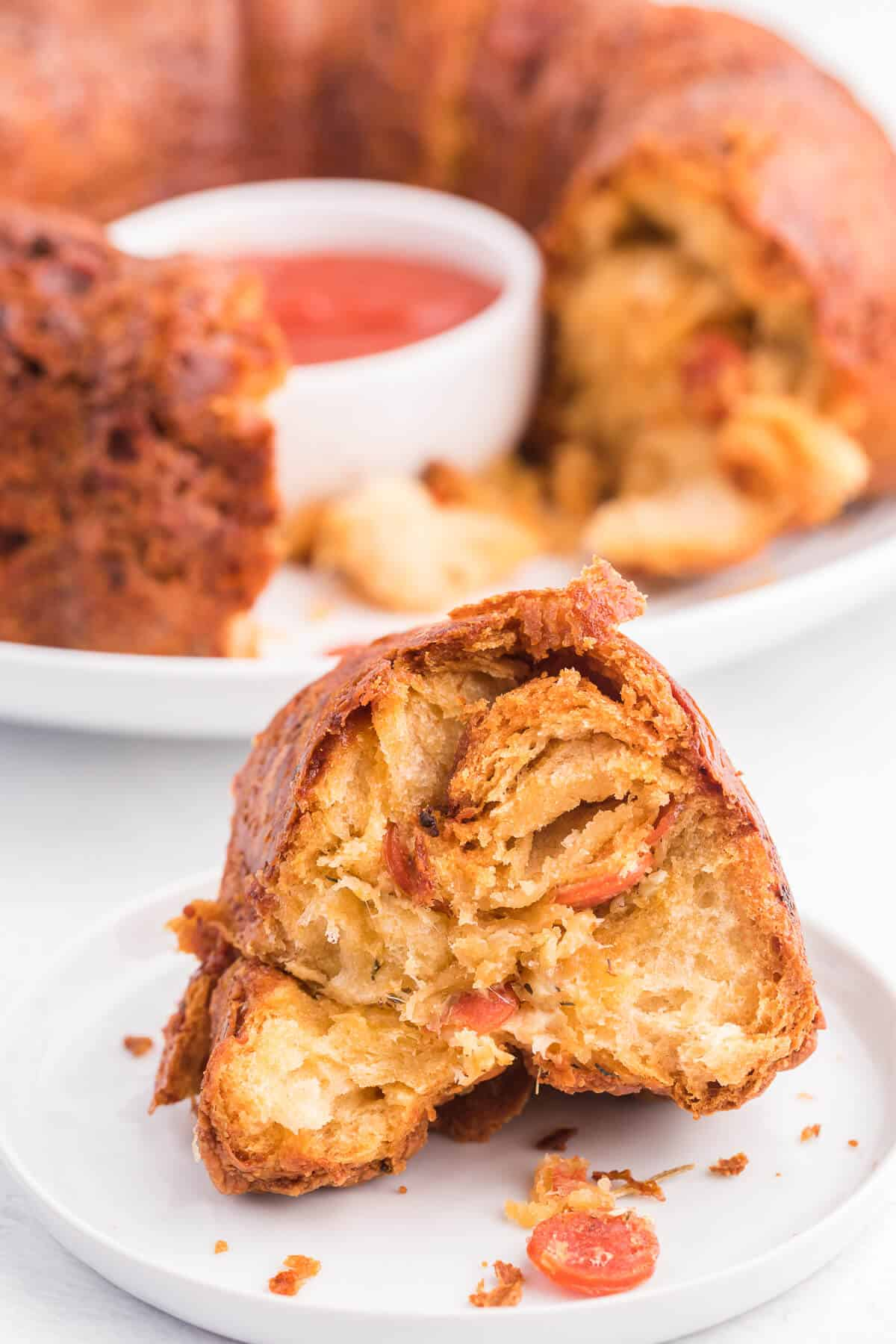 Pizza Monkey Bread Recipe - This pull apart game day recipe is simple to make in a bundt pan. Crescent roll dough, pepperoni and mozzarella cheese are combined to make the most delicious Italian-style appetizer. Serve with some pizza sauce for easy dipping!
