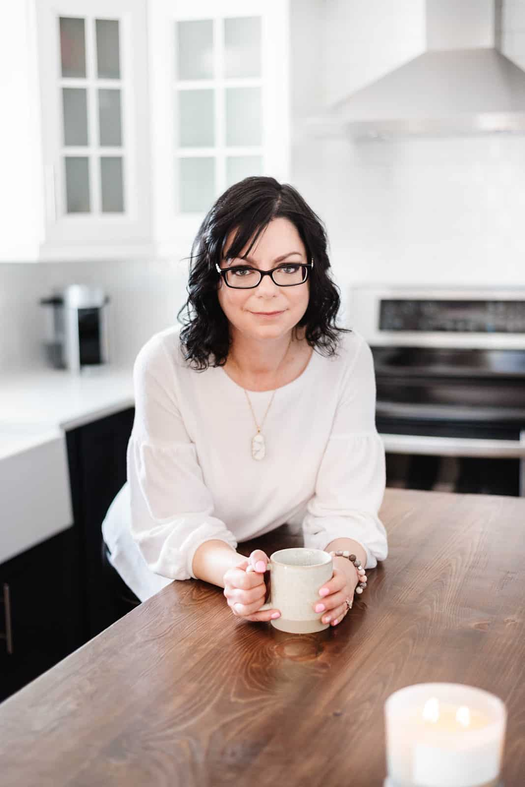 Food blogger Stacie Vaughan holding a coffee cup on a kitchen counter.