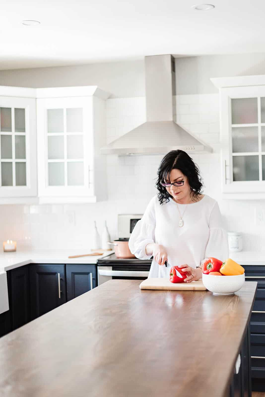 Food blogger Stacie Vaughan chopping a red pepper on a counter.