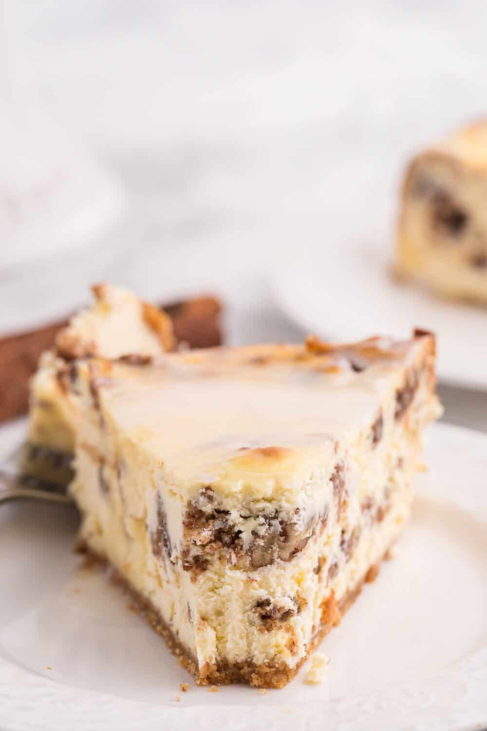 a slice of cinnamon roll cheesecake with a bite off the end