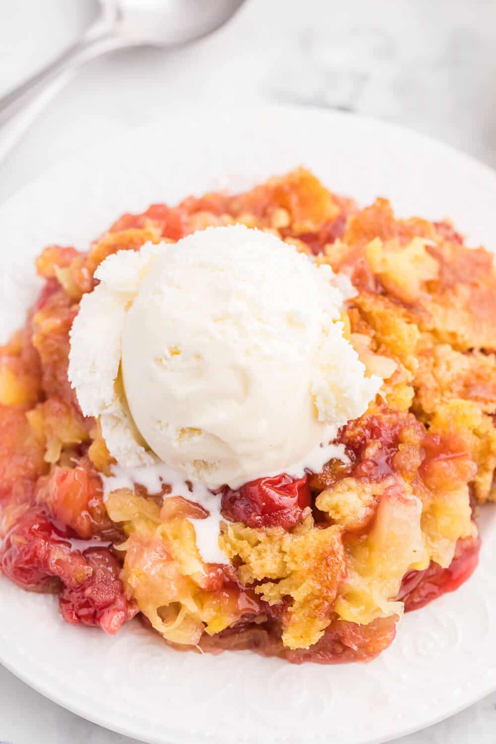 Cherry Pineapple Dump Cake Recipe - Made in 1 pan and only 4 ingredients in this quick and easy dessert recipe. Short prep time and no mixing! Perfect for potlucks and cookouts.