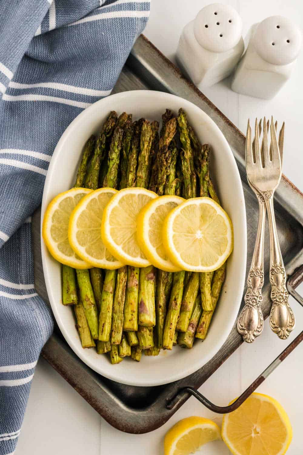 Asparagus topped with sliced lemon in a white casserole dish
