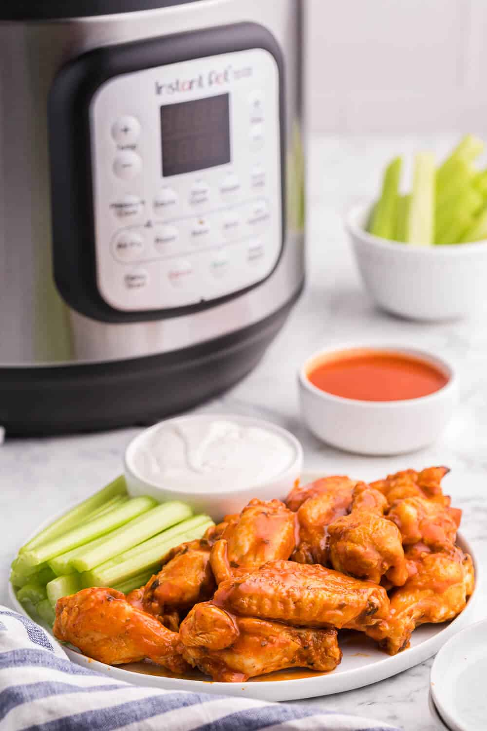 A plate of buffalo chicken wings with celery and dip and an air fryer in the background