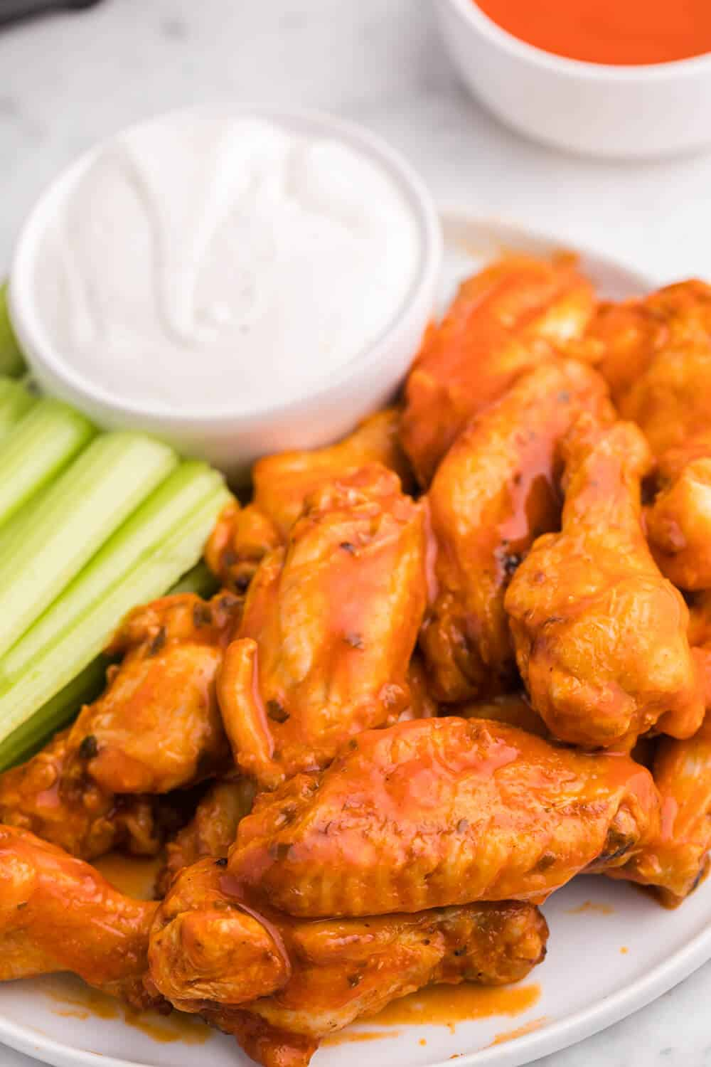 buffalo chicken wings on a plate with celery sticks and dip